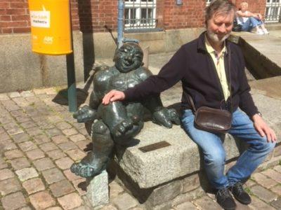 Vor dem Opernhaus steht eine Granitbank, auf der er sitzt, der gute Geist, in Bronze geschaffen von Tauno Kangro. Ud Jürgen Trinkus hat sich dazu gesetzt, um dem Rathausglockenspiel zu lauschen